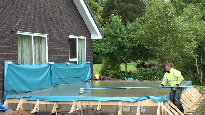 The concrete being floated flat using a big blue magnesium float with long handles