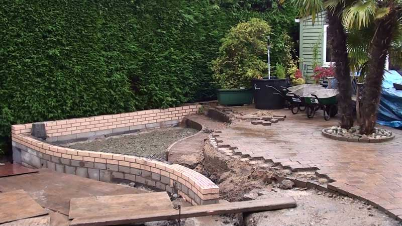 New retaining brick walls are constructed for the change in levels within the patio