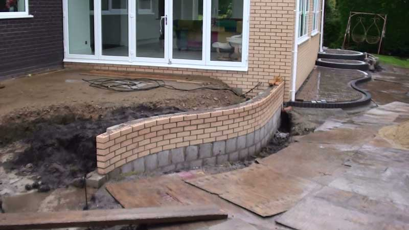 New curved retaining brick wall which is capped off using Marshalls Fairstone golden sand multi bull nose step units