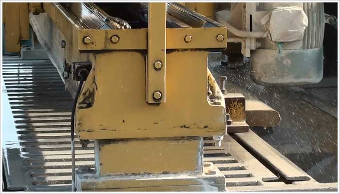 This machine puts the bull nose on the straight sections of Marshalls bull nose step units. It works using an abrasive wheel that gently grinds away the stone to create the bull nose front.