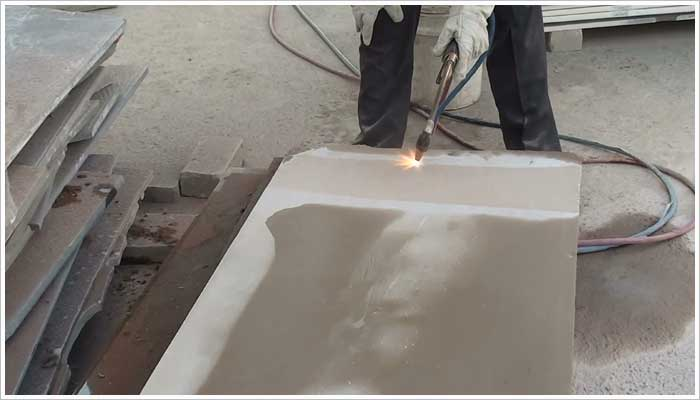 Applying a flamed finish to the surface of the stone buy brushing the tip of the flaming lance against the stone while moving the head from side to side across the stone at a steady but consistent speed. This can also be done 'in-line' using an automated flaming process.