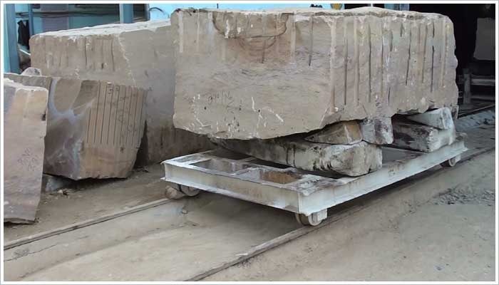 Steel trolly with large block of stone securely held in place with timber wedges