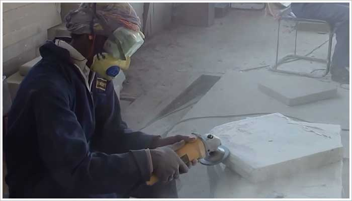 Forming the bull nose edge with a hand held grinder. It's very dusty work so the operative is well equipped with personal protective equipment