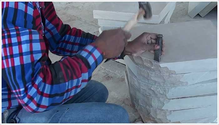 Removing the bulk of the stone to form the quadrant shape, first the stone is marked using a template then carefully chipped away using a hammer and chisel