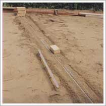using steel poles as a guide to screed the sand